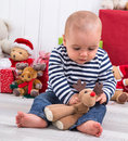 First christmas baby with presents in background is playing a plush reindeer or elk Royalty Free Stock Photos