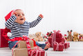 First christmas baby unwrapping a present smiling and happy Royalty Free Stock Photography