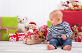 First christmas baby unwrapping a present and teddy bears in background Stock Photo