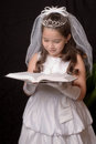 First communion a studio portrait of a young girl reading the bible for isoltaed on black Stock Photography