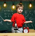 First former confused with studying, learning, education. Child with confused expression near microscope. Primary school
