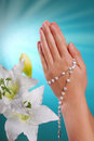 The first holy communion amen hands of a girl going to prying with rosary on blue background Stock Photo