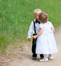 First love first kiss baby girl kisses baby boy both are dressed as groom and bride Stock Photos