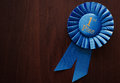 First place winners rosette or badge in pleated blue ribbon with central text to be awarded as a prize in a competition race or Royalty Free Stock Photos