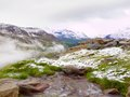 First snow in alps touristic region fresh green meadow with rapids stream peaks of alps mountains in background foamy water is Royalty Free Stock Images