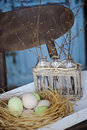 First spring twigs in bottles in basket with easter eggs in nest Royalty Free Stock Photo