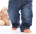 First steps little baby feets in jeans isolated on white with a teddy bear boy Royalty Free Stock Photos
