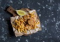 Fish balls and potato chips on rustic cutting board on a dark background.