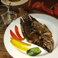 Fish carp served with vegetables sweet pepper and cucumber on a plate