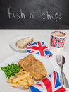 Fish and chips with a cup of tea bread and butter and union jac meal english peas slice mug in jack mug british flags on rustic Stock Photos