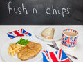 Fish and chips with a cup of tea bread and butter and union jac meal english peas slice mug in jack mug british flags on rustic Royalty Free Stock Image