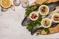 Fish dish cooking with various ingredients. Raw rainbow trout with lemon. Royalty Free Stock Photo