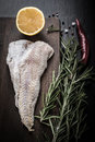 Fish filet, rosemary, red chili pepper, half a lemon and sea sal Royalty Free Stock Photo