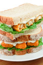 Fish finger sandwich detail fresh close up on a white serving plate Royalty Free Stock Photography