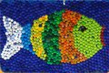 Fish mosaic deocoration made of cororful plastic bottle caps . S Royalty Free Stock Photo