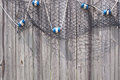 Fish net with floats on wooden fence blue and white hanging a Royalty Free Stock Image