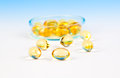 Fish oil capsules on blue background Stock Photo