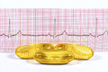 Fish oil capsules and ECG on white background. Royalty Free Stock Photo
