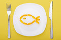 Fish oil soft gels lying on a plate white porcelain in the form of yellow background Royalty Free Stock Photography