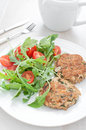 Fish patties with parsley and arugula tomato salad dinner Stock Photo