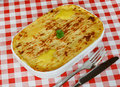 Fish pie on cafe table traditional homemade in a casserole dish with crispy mashed potato the top a red gingham tablecloth Stock Image