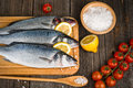 Fish sea bass with spices salt lemon on wooden hardboard prepared for cooking Royalty Free Stock Image
