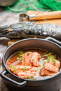 Fish soup made ​​of fresh vegetables and salmon on old wooden table Royalty Free Stock Photography