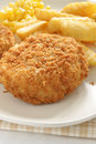 Fishcake with chips and sweet corn Stock Photo