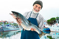 Fisher holding a big atlantic salmon fish in the fishing harbor Stock Photos