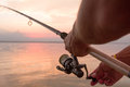 Fisher's hands holding reel, fishing at the sunset Royalty Free Stock Photo