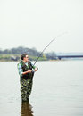 Fisherman angling on the river mature Stock Images