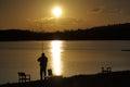 Fisherman captured at sunrise on a beautiful lake Royalty Free Stock Image
