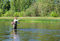 Fisherman catches of chub  fly fishing in the Chusovaya river Royalty Free Stock Photo