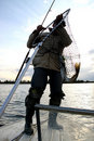 Fisherman with a catching fish Royalty Free Stock Image
