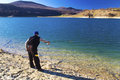Fisherman fishing on blue lake Royalty Free Stock Photo