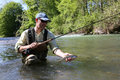 Fisherman fishing brown trout Royalty Free Stock Photo
