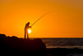 Fisherman fishing at dawn early summer morning Royalty Free Stock Photo