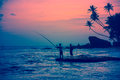 Fisherman and friend at unawatuna beach silhouette of a his palm trees large rock against sunset on the of western coast of sri Stock Photography
