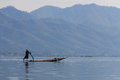 Fisherman inle lake in myanmar burmar with leg rowing mountain background Stock Photo