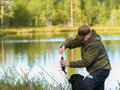 Fisherman and perch get a with rod reel horizon image Royalty Free Stock Photo