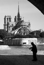 Fisherman on river Seine and Notre Dame de Paris, Paris, France Royalty Free Stock Photo