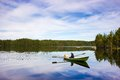 Fisherman sails on a green boat on the lake Royalty Free Stock Images