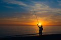 Fisherman on the shore of the sea system the fishing rod