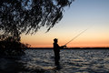 Fisherman silhouette at sunset Royalty Free Stock Photo