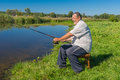 Fisherman sitting on a wicker stool with spinning rod and ready to catch fish in small river Merla in central Ukraine Royalty Free Stock Photo