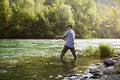 Fisherman standing near river and holding fishing rod mid adult man on holidays on relaxing trout Royalty Free Stock Photography