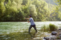 Fisherman standing near river and holding fishing rod mid adult man on holidays on relaxing trout Stock Photo