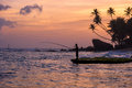 Fisherman at unawatuna beach silhouette of a palm trees and large rock against sunset on the of western coast of sri lanka Stock Image