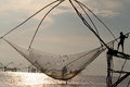 Fisherman working using fishing net early in morning during sunrise Royalty Free Stock Photo