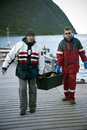 Fishermen carrying fish box Royalty Free Stock Photos